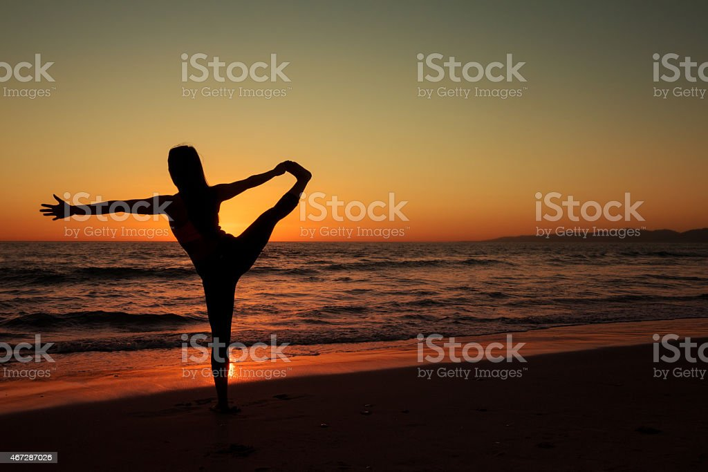 Silhouette of woman doing yoga on sandy beach at sunset stock photo