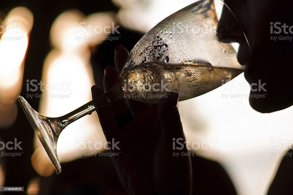 Silhouette of woman drinking wine stock photo