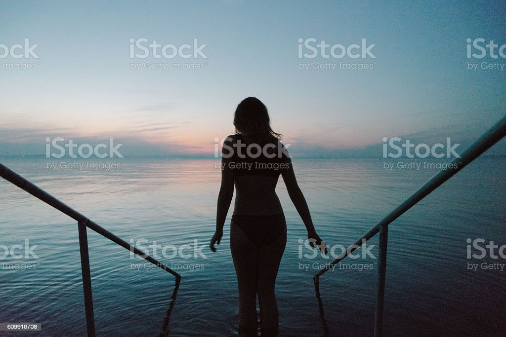 Silhouette of woman going to water stock photo