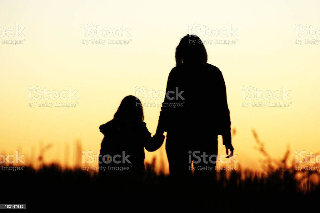 Silhouette of woman holding girls hand at sunset royalty-free stock photo