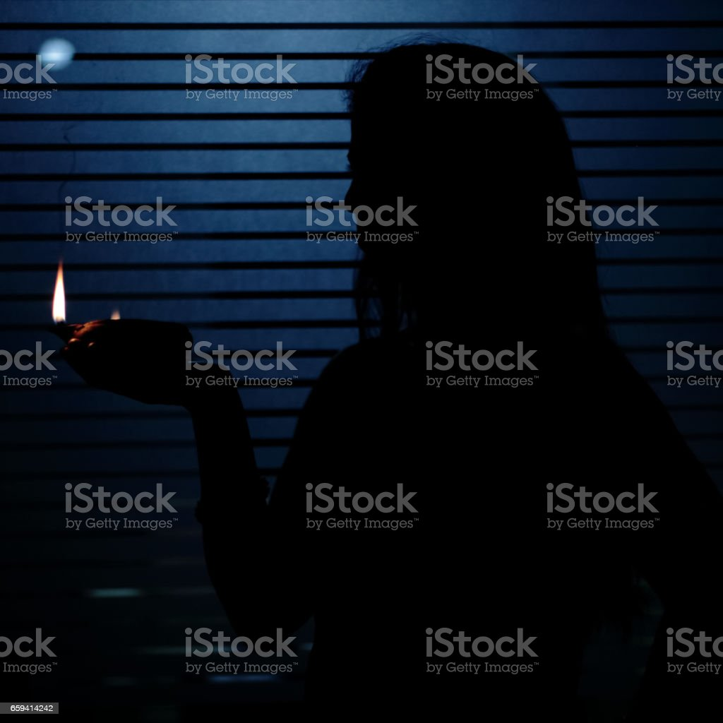 Silhouette of Woman Holding Oil Lamp stock photo