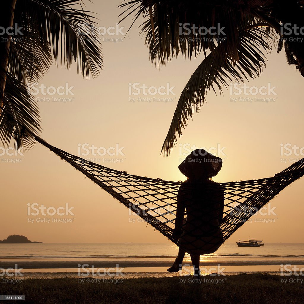 silhouette of woman in hammock stock photo