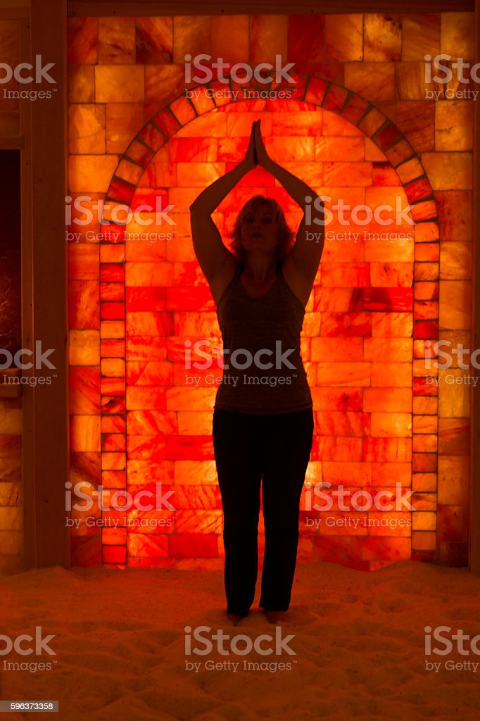 Silhouette of woman in yoga pose against red bricks stock photo