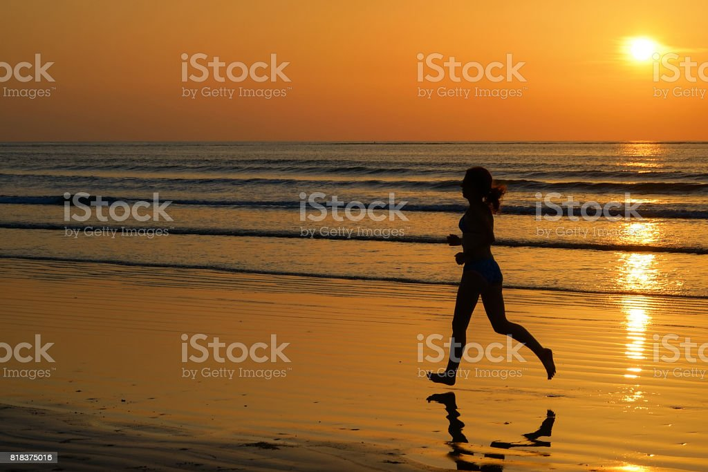 Silhouette of woman jogger running on sunset beach with reflection, fitness and sport concept stock photo