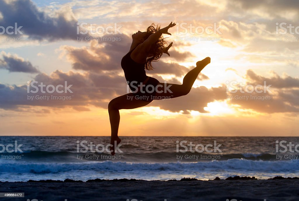 Silhouette of woman jumping on a beach stock photo
