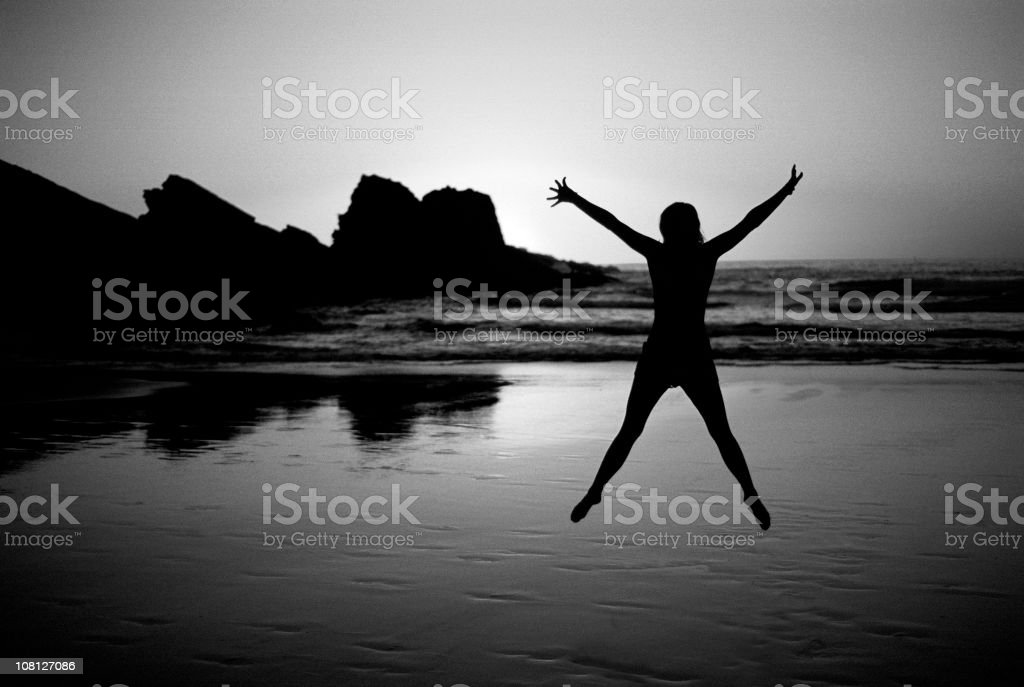 Silhouette of Woman Jumping on Beach at Sunset stock photo