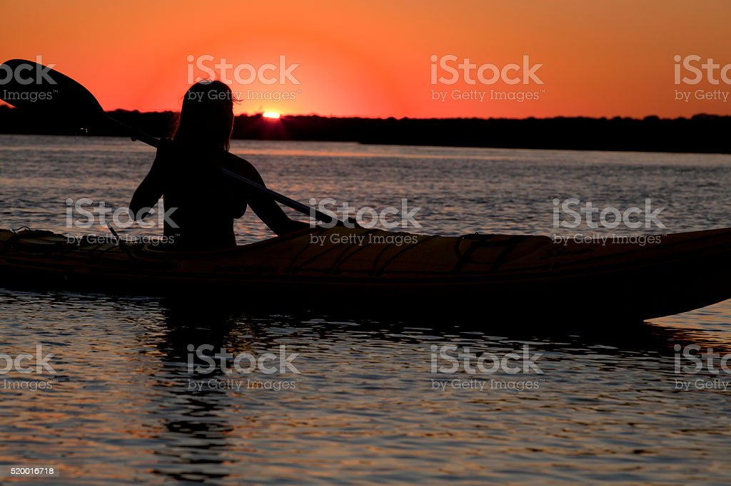 Silhouette of woman kayaking in the ocean stock photo