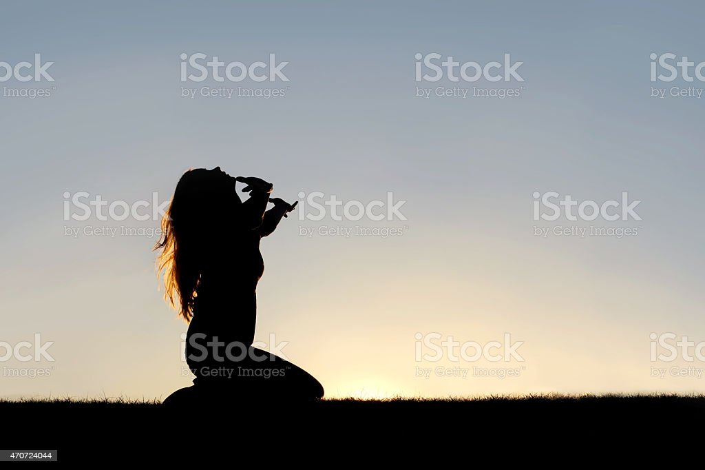 Silhouette of Woman Kneeling in Prayer and Surrender stock photo