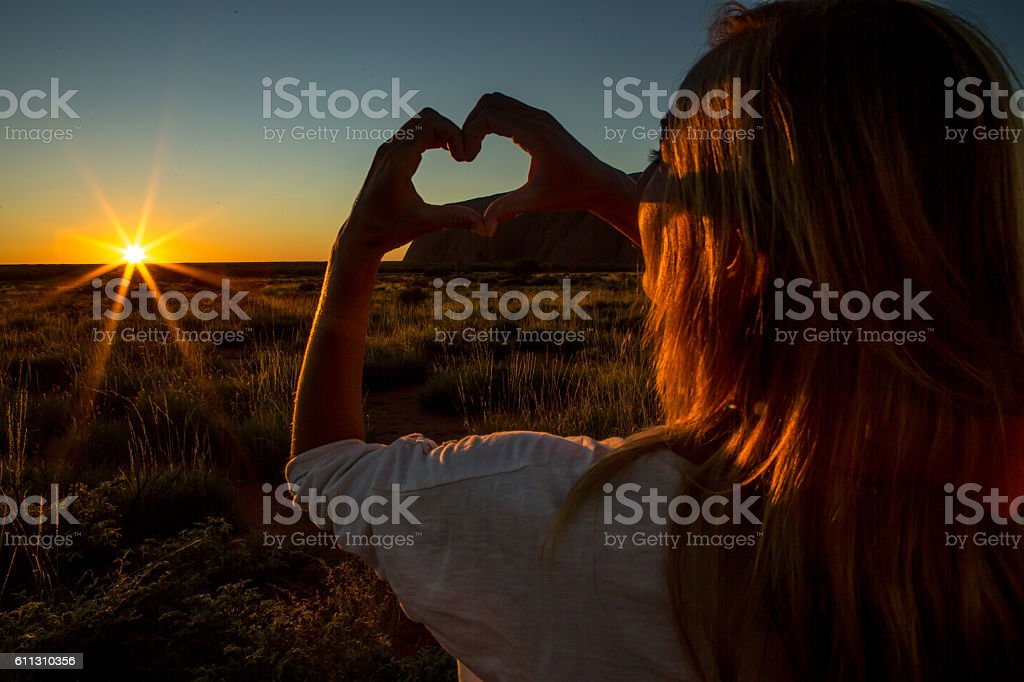 Silhouette of woman making heart shape finger frame on sunset stock photo