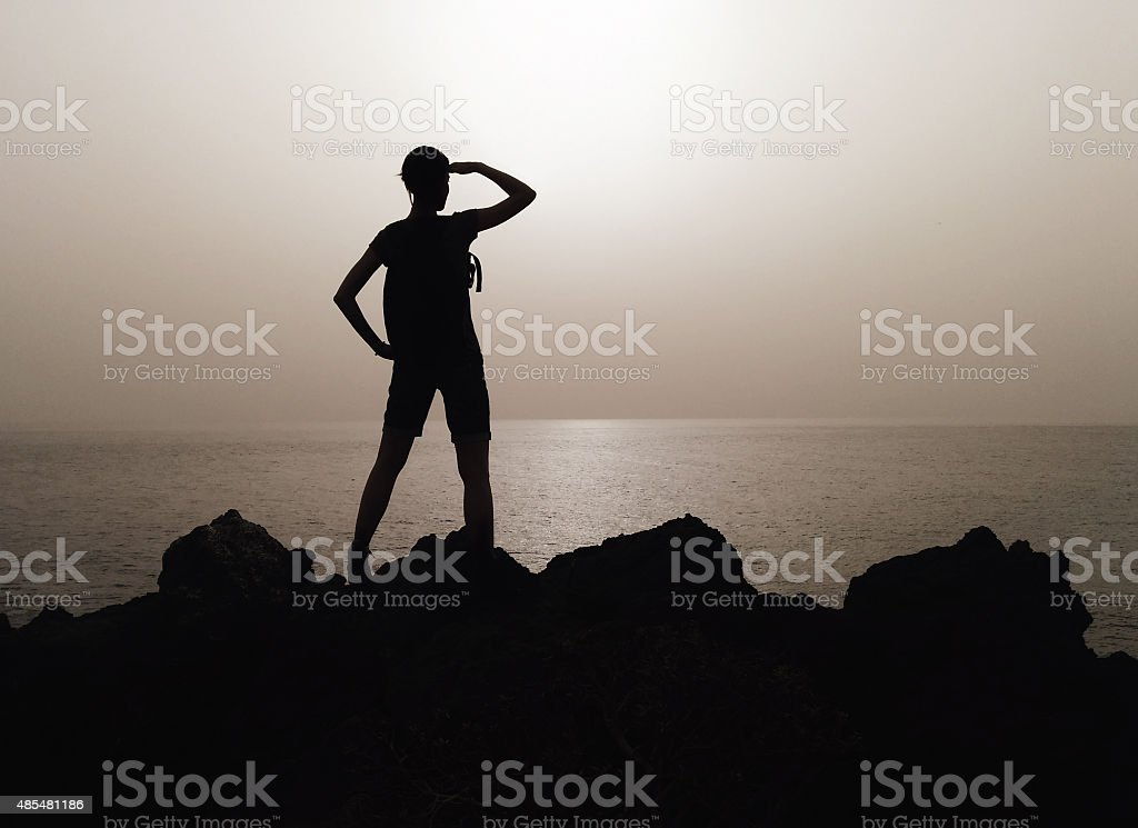 Silhouette of woman on a top of mountain stock photo