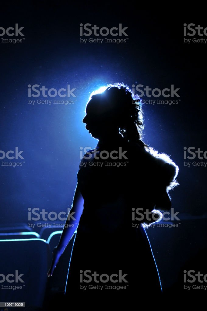 Silhouette of Woman on Blue Background stock photo
