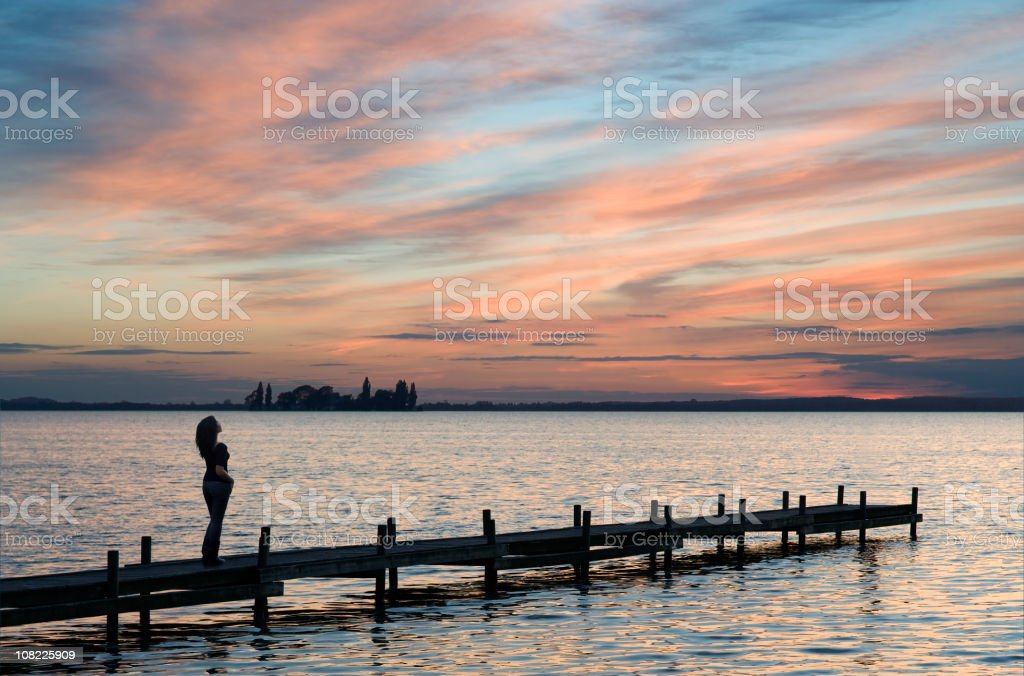 Silhouette of woman on lakeside jetty with majestic sunset cloudscape royalty-free stock photo