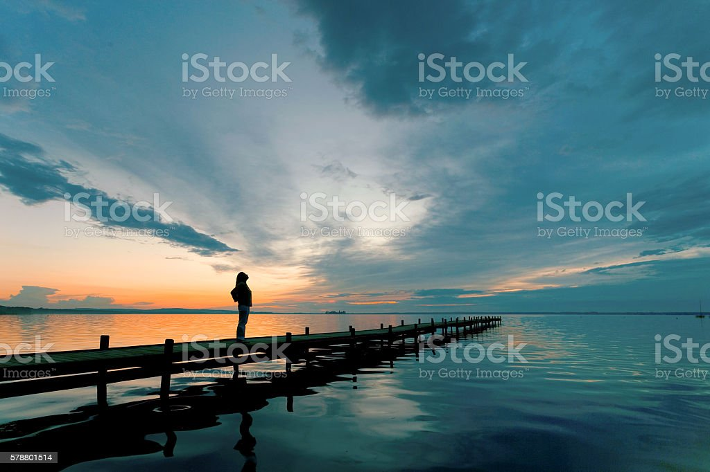 Silhouette of Woman on Lakeside Jetty with majestic Sunset Cloudscape stock photo