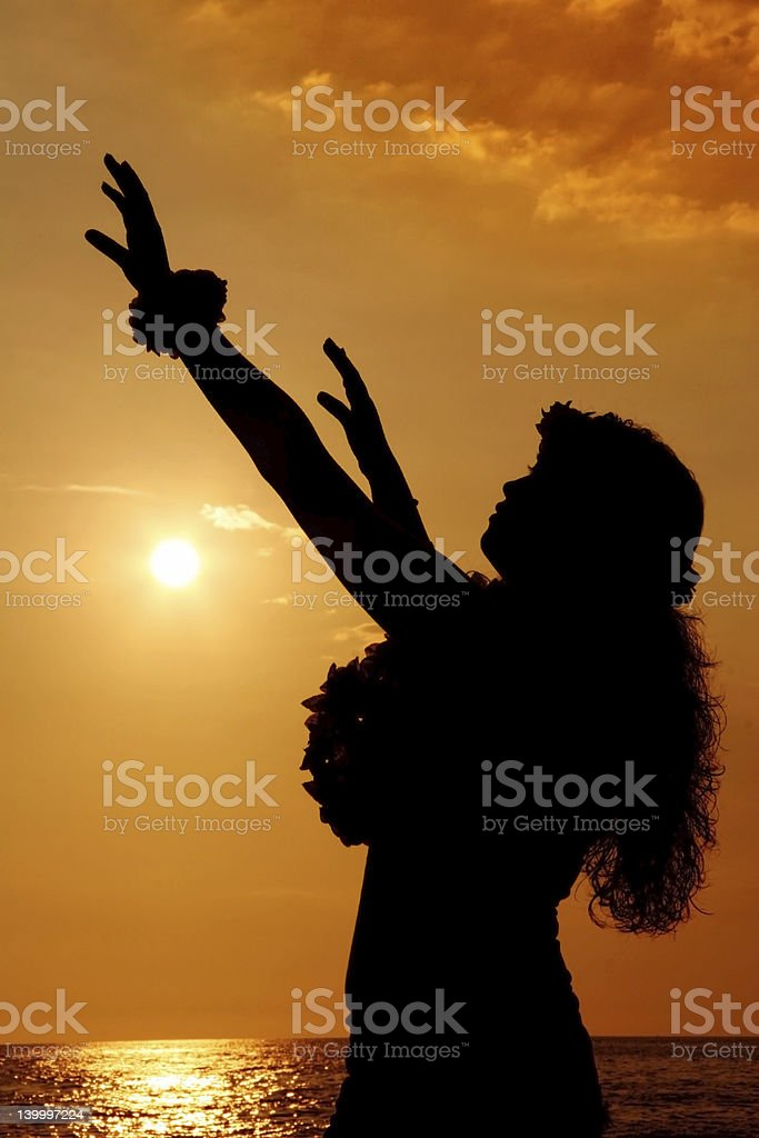 Silhouette of woman performing hula in orange sunset stock photo