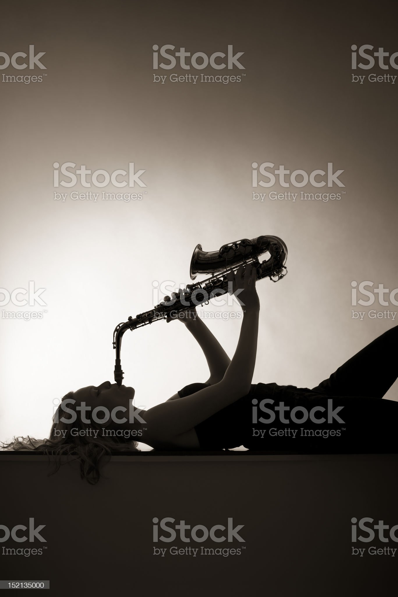 Silhouette of woman playing saxophone, sepia toned. royalty-free stock photo