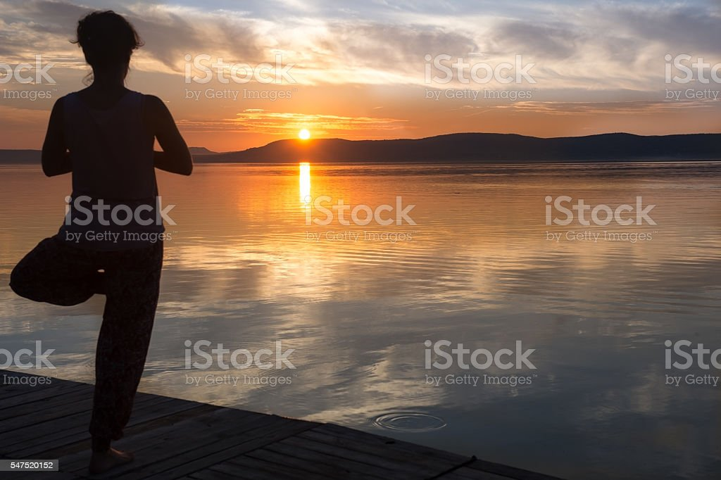 Silhouette of woman practicing yoga and meditating on the lake stock photo