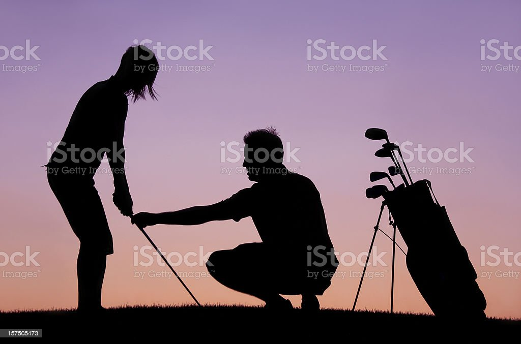 Silhouette of Woman Recieving Golf Lesson From Instructor stock photo
