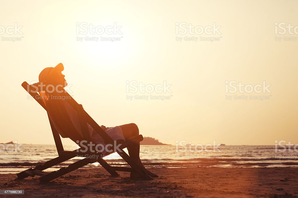 silhouette of woman relaxing on the beach at sunset stock photo