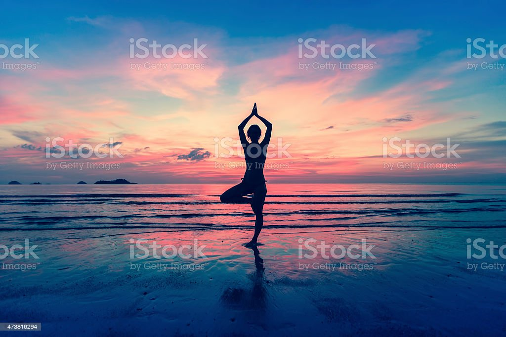 Silhouette of woman standing at yoga pose on the beach stock photo