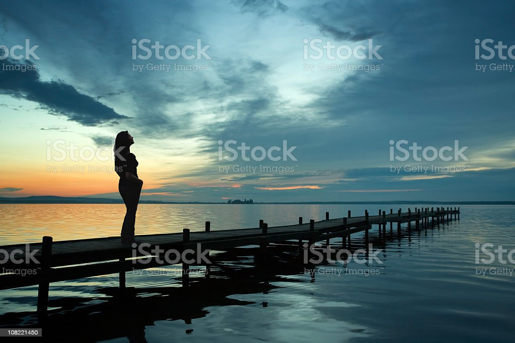 Silhouette of Woman Standing on Lakeside jetty at Sunset cloudscape royalty-free stock photo