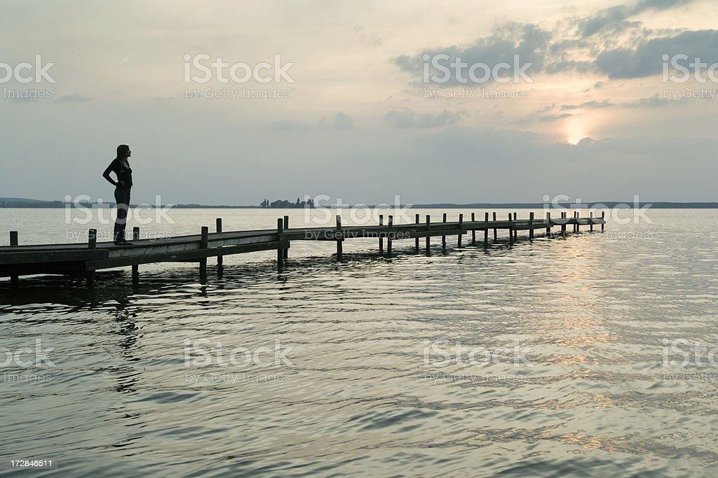 Silhouette of woman standing on lakeside jetty at sunset (XXL) stock photo
