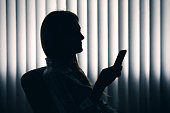 Silhouette Of Woman Texting In The Dark