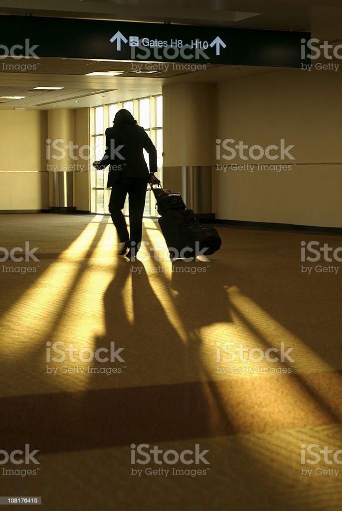 Silhouette of Woman WalkingWith Luggage Towards Airport Gate royalty-free stock photo