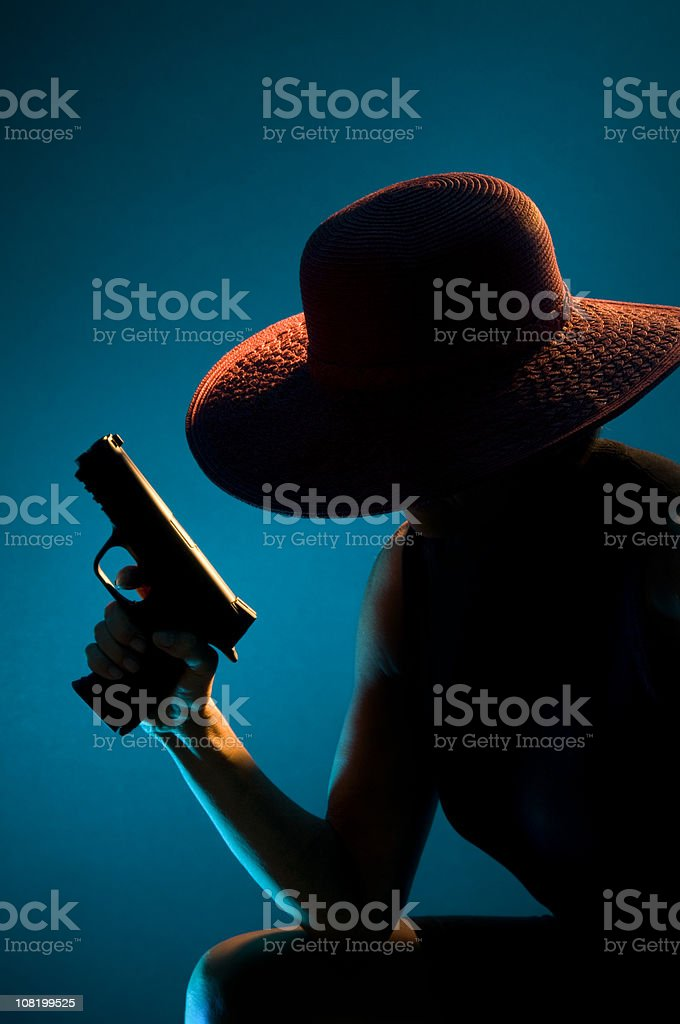 Silhouette of Woman Wearing Hat and Holding Gun royalty-free stock photo