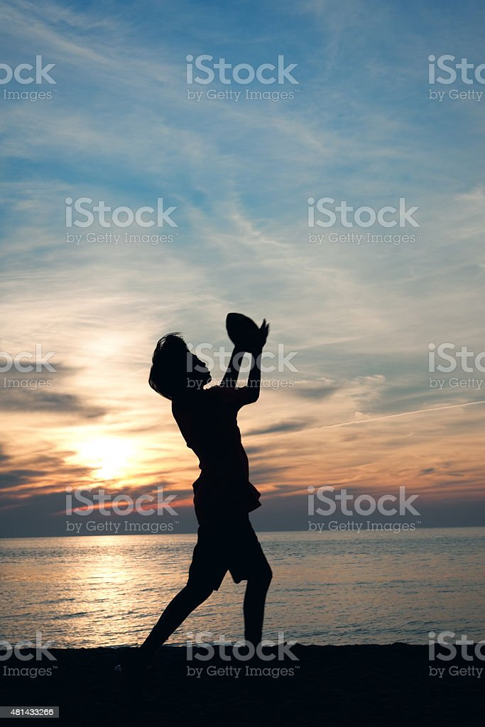 Silhouette of Young Boy Catching Football on Beach stock photo