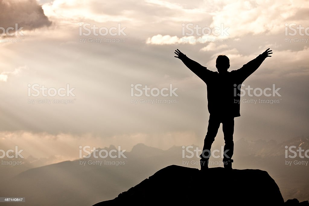 Silhouette of Young Boy Happy Caucasian Boy in the Mountains stock photo