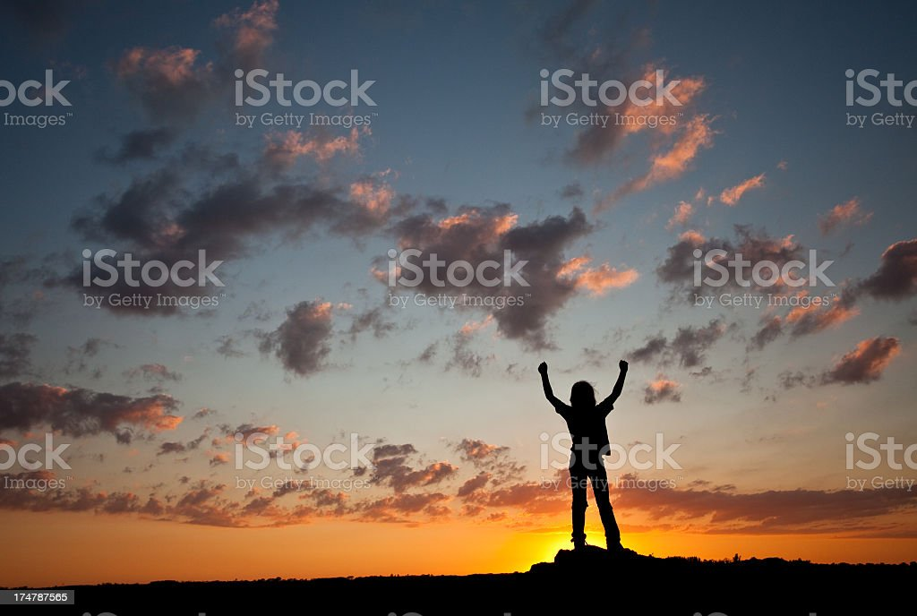Silhouette of Young Boy Raising Arms royalty-free stock photo