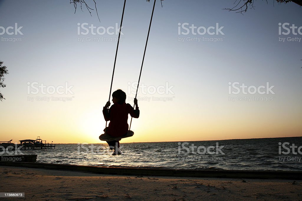 Silhouette of Young Boy Swinging on Swingset Playing at Sunset stock photo
