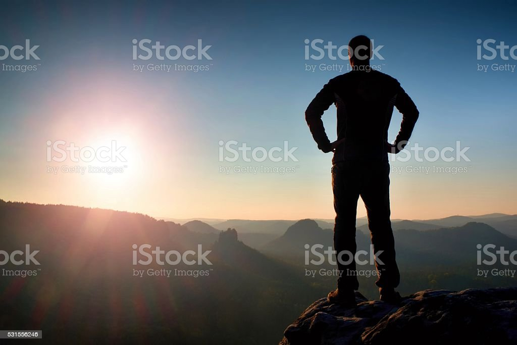 Silhouette of Young Confident Man Standing with Hands on Hips stock photo
