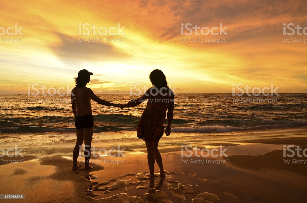 silhouette of young couple in love on beach when sunset royalty-free stock photo