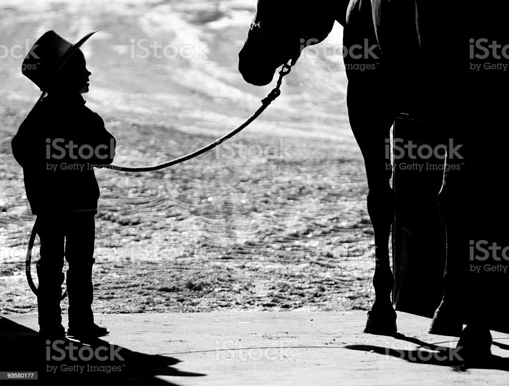 Silhouette of young cowboy and his horse stock photo