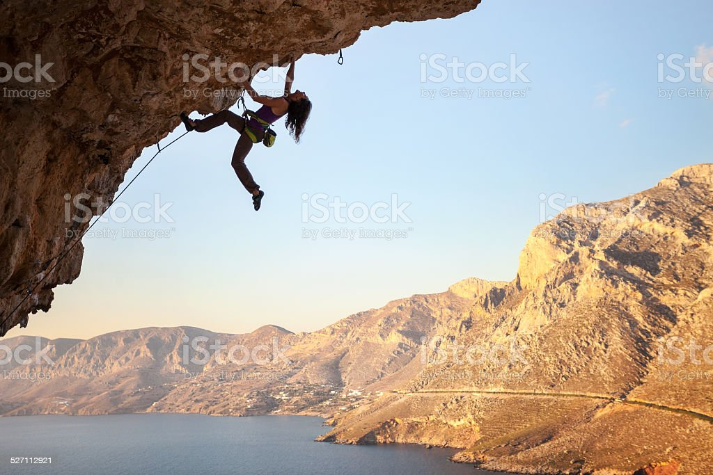 Silhouette of young female rock climber on a cliff stock photo