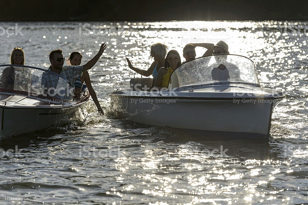 Silhouette of young friends in motorboats royalty-free stock photo