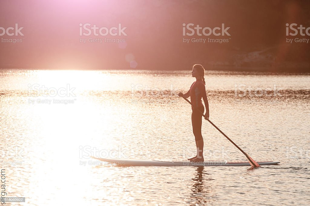silhouette of young girl paddle boarding at sunset01 stock photo