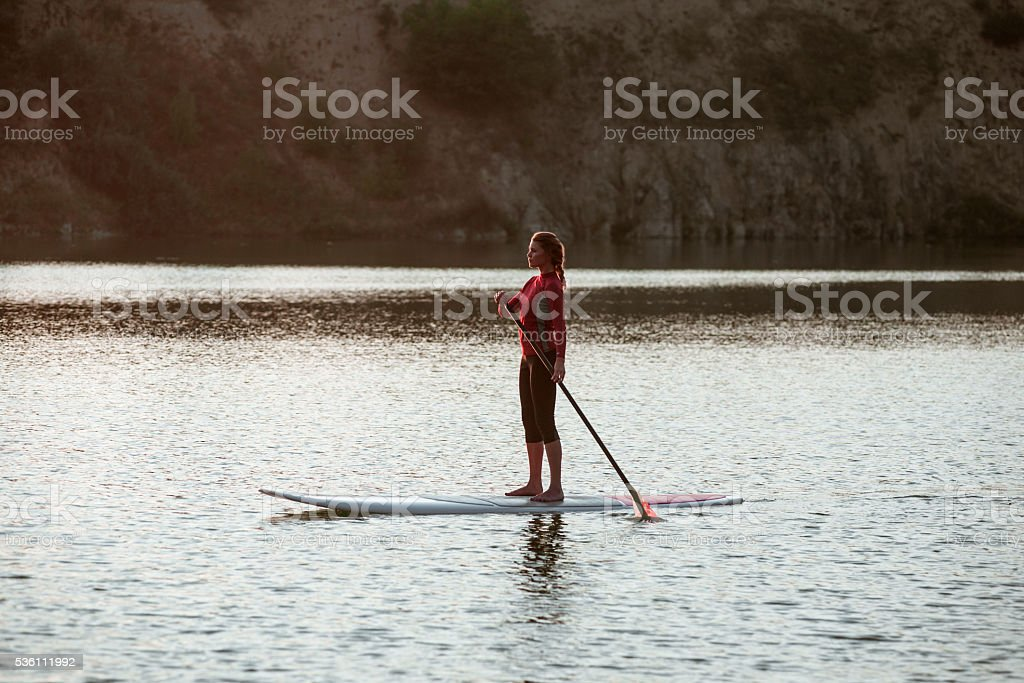 silhouette of young girl paddle boarding at sunset11 stock photo