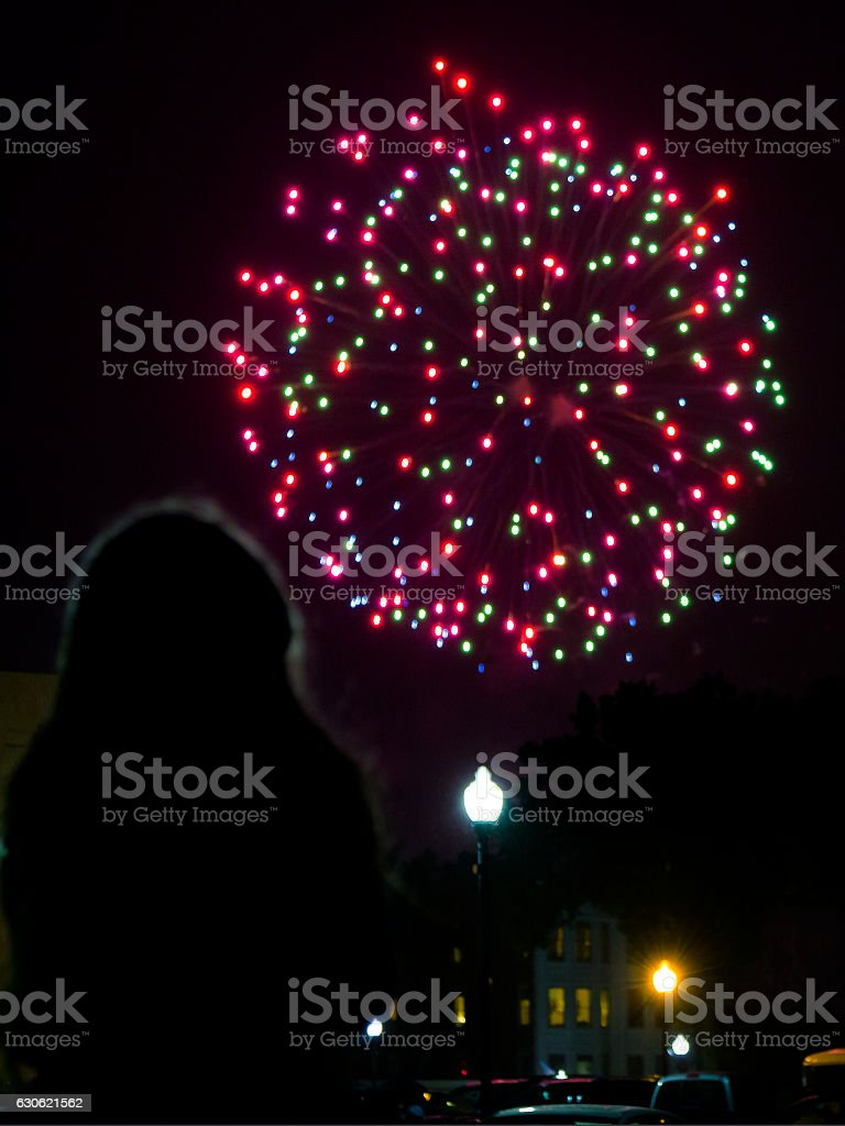 Silhouette of young girl watching 4th of July fireworks stock photo