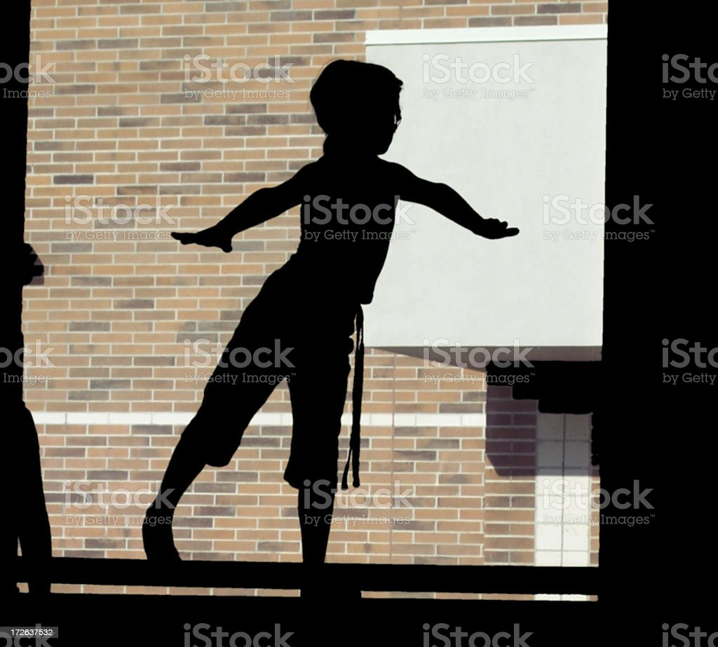 Silhouette of young gymnast on balance beam stock photo