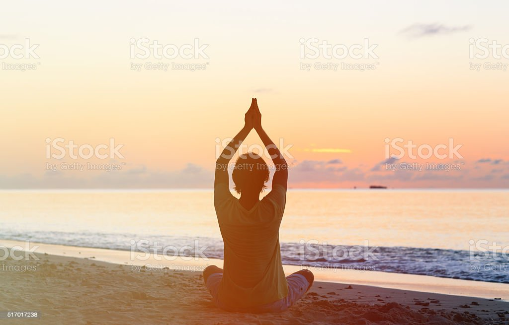 Silhouette of young man doing yoga at sunset stock photo