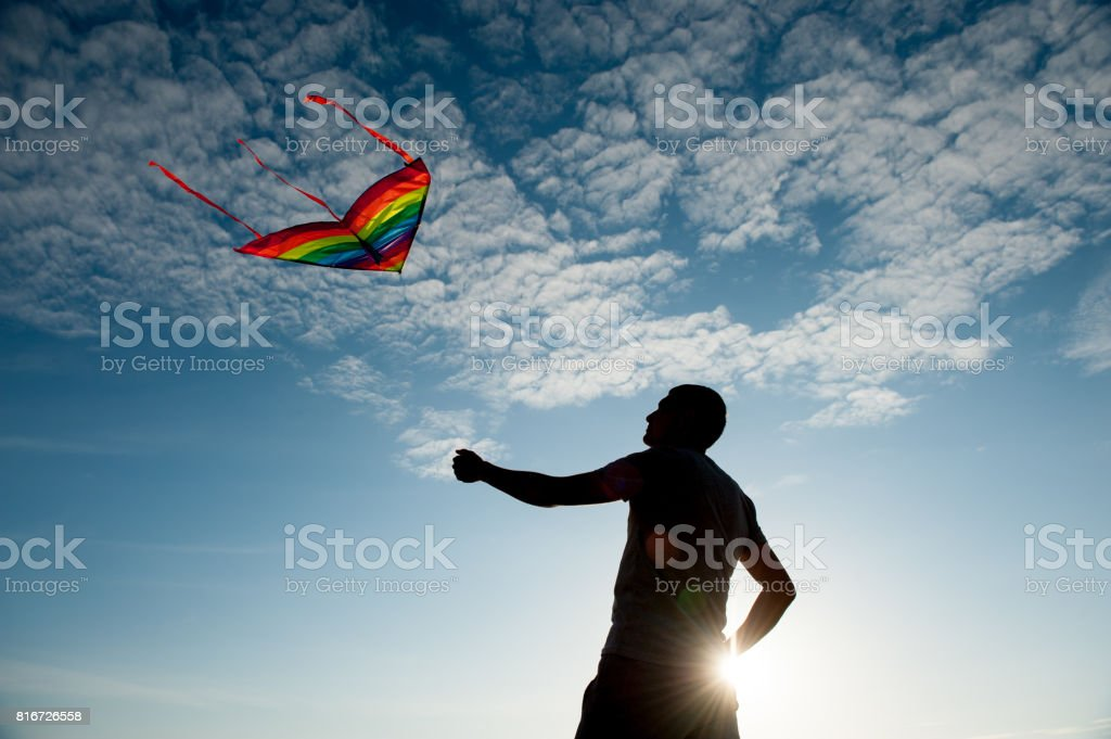 Silhouette of young man holding a kite flying in a blue sky with clouds at sunset stock photo