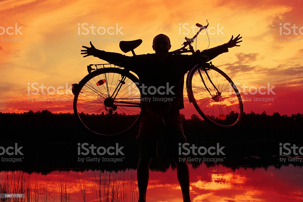 Silhouette of Young Man Holding Bike royalty-free stock photo