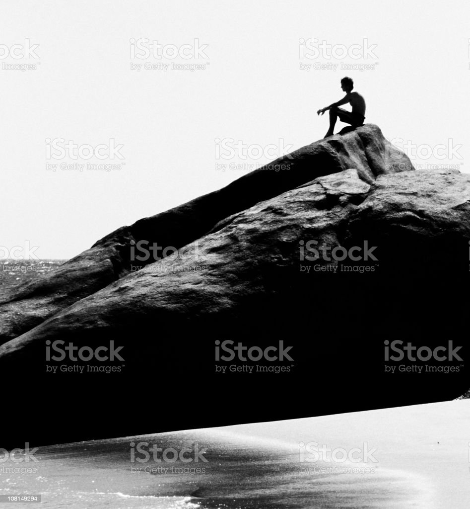 Silhouette of Young Man Sitting on Coastal Rock at Beach royalty-free stock photo