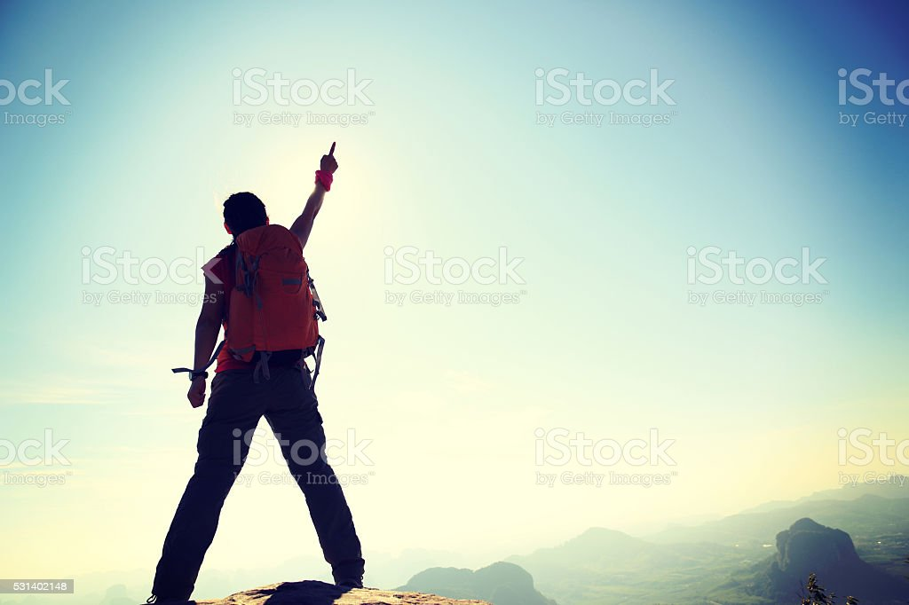 silhouette of young successful woman hiker on mountain peak stock photo