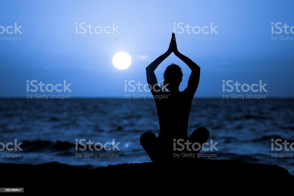 Silhouette of Young Woman Doing Yoga stock photo