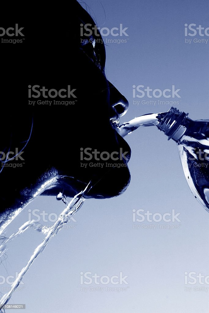 SIlhouette of Young Woman Pouring Water Into Mouth, Toned royalty-free stock photo