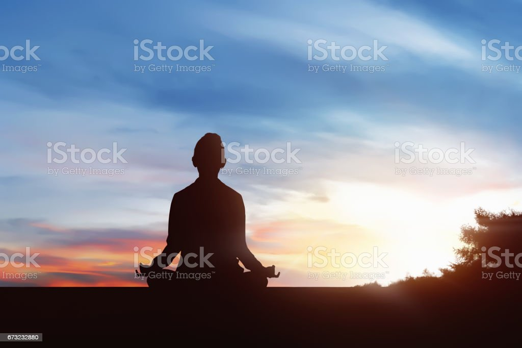Silhouette of young woman practicing yoga in outdoor stock photo
