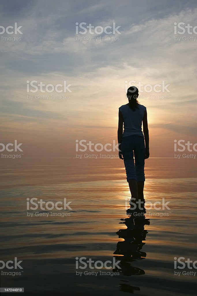Silhouette of young woman standing in a water stock photo